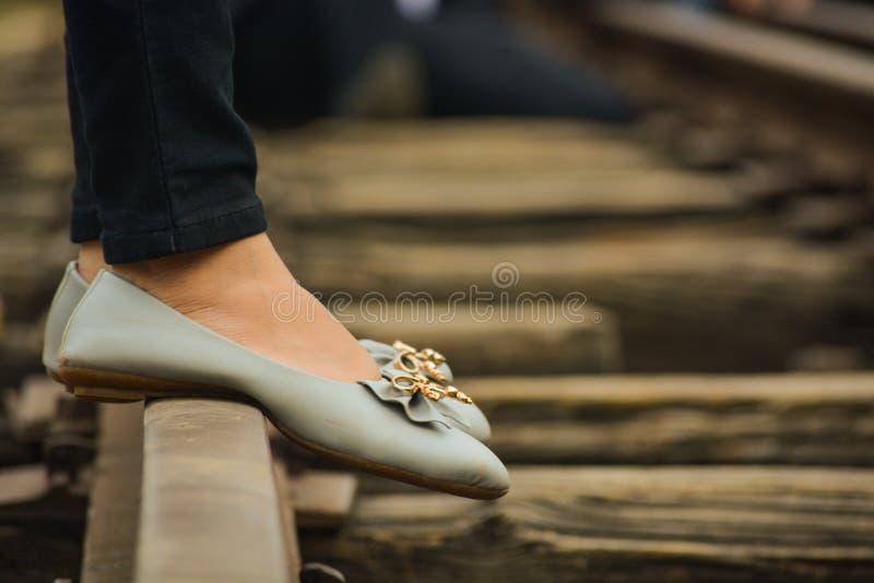 Foots av ett flickaanseende på en järnvägsspår arkivfoto
