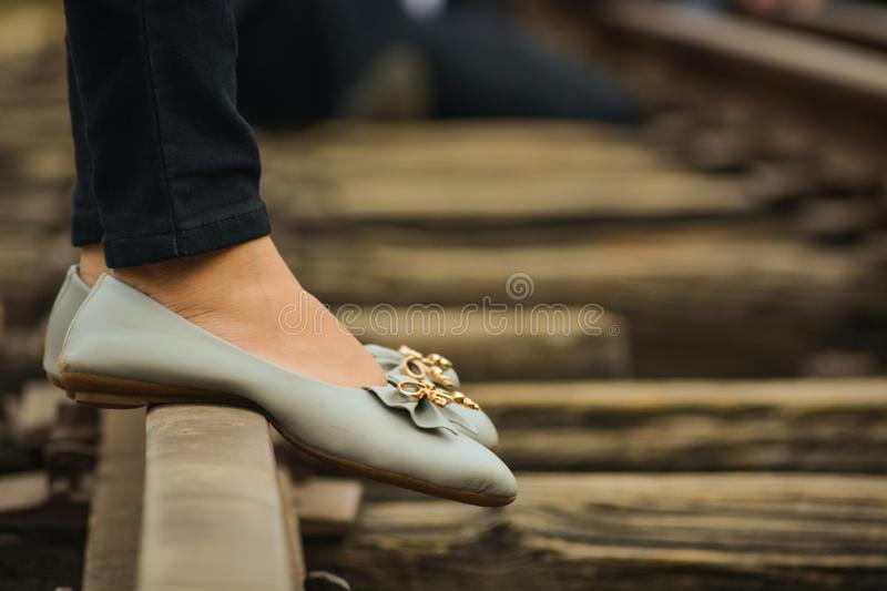 Foots of a girl standing on a railway track stock photo