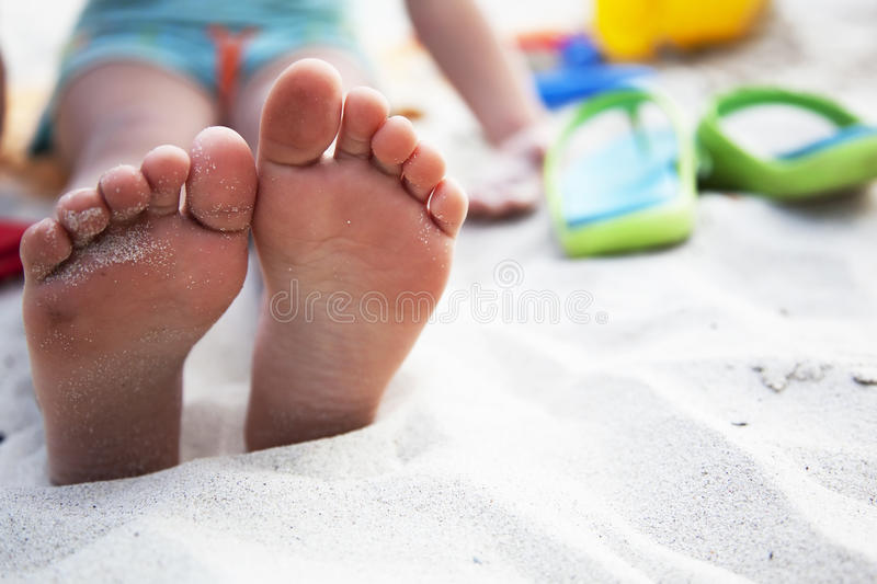 Foots of little girl at the beach and slates nearb royalty free stock image