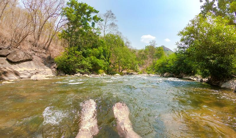 Foots in water waterfall and waterfall landscape,sunny sky,Relaxing His Feet. Foots in water waterfall and waterfall landscape, sunny sky, Relaxing His Feet royalty free stock images