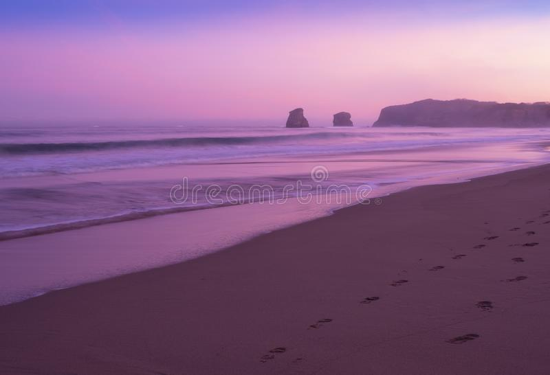 Footsteps on the beach with the first lights of dawn over the sea of Hendaia beach. Footsteps on the beach with the first lights of dawn over the sea of Hendaia stock photo