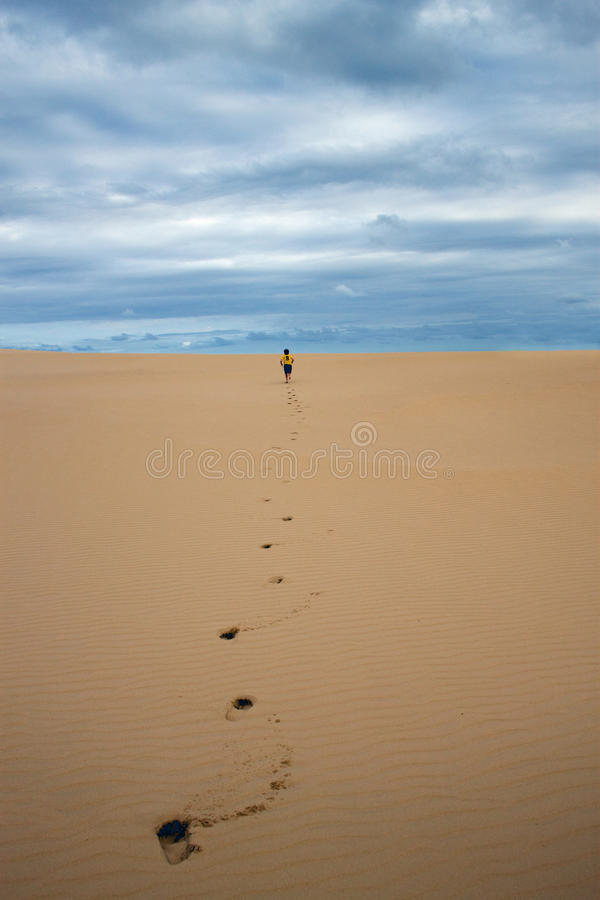 Footsteps Future. A boy runs into an endless sand hill which represents his future. Footsteps in untouched sand define his path. Vertical image with grainy royalty free stock photo