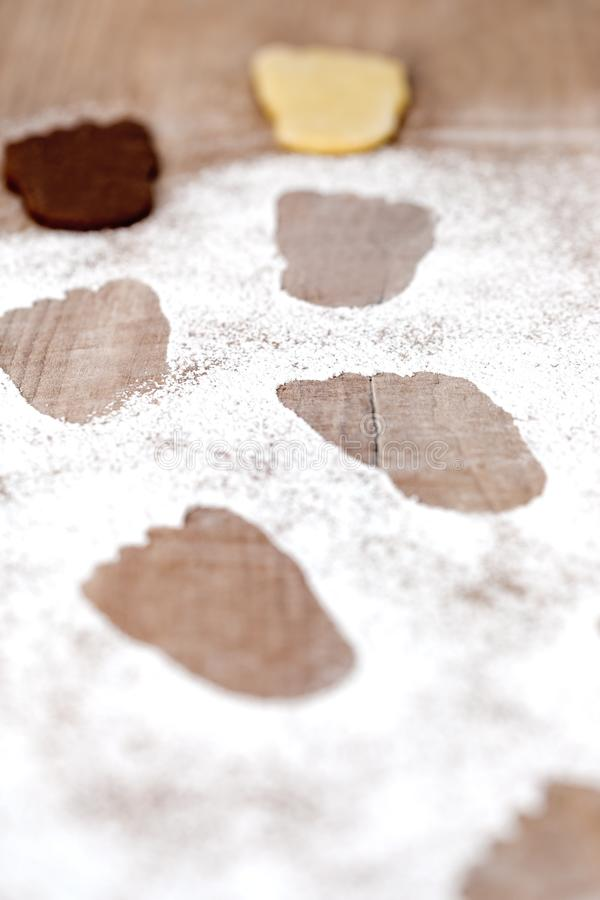 Footsteps on icing sugar, dark and white foot shaped cookies in the background. Footprints or Footsteps on icing sugar, dark and white foot shaped cookies in the royalty free stock image