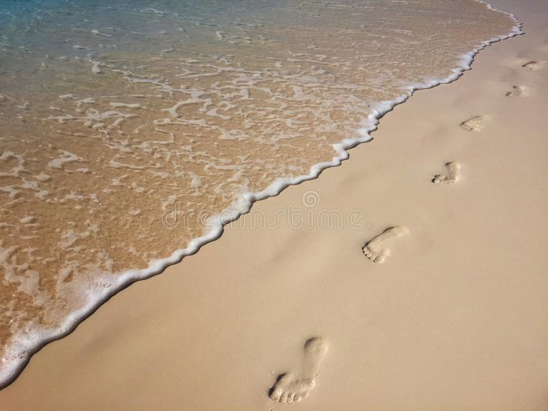 Footsteps in the sand. And the sea tide royalty free stock photos