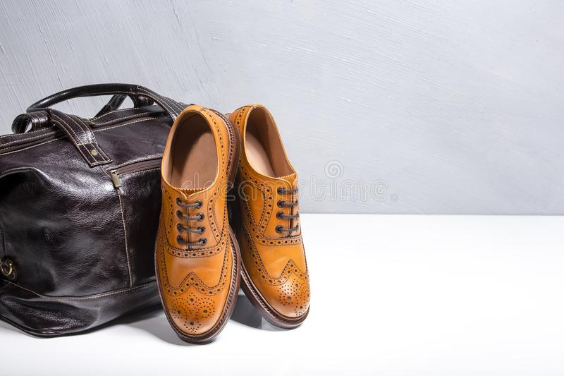 Footwear and Accessories Concepts. Closeup of Male Tanned Full B. Roggued Oxford Calf Leather Shoes Along With Dakr Brown Leather Travel Bag on White. Horizontal royalty free stock photography