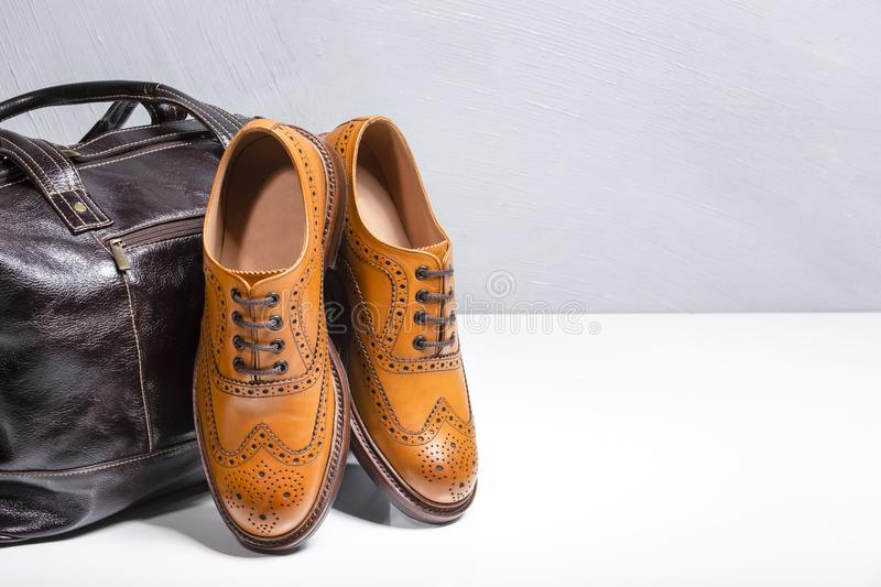 Full Broggued Oxford Calf Leather Shoes Along With Dark Brown Leather Travel Bag. Footwear and Accessories Concepts. Closeup of Male Tanned Full Broggued Oxford stock image