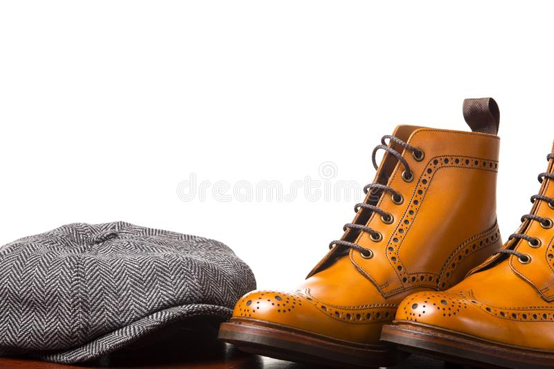 Footwear Compositions Made Up of Men`s Fashionable Tanned Brogues. Footwear Compositions Made Up of Mens Fashionable Tanned Brogues Boots and Casual Cap Laid stock photo