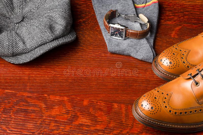 Footwear Compositions Made Up of Mens Fashionable Tanned Brogues. Boots, Cap, Pair of Socks and Mens Watch Placed Together. Over Wooden Background.Horizontal stock photos