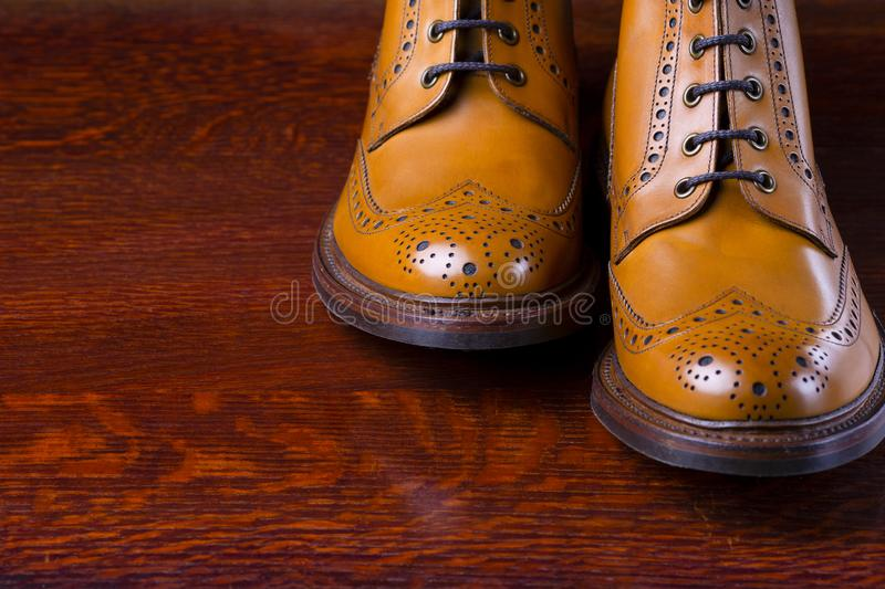 Footwear Compositions Made Up of Mens Fashionable Tanned Brogues. Boots Over Wooden Background. Horizontal Image stock photo