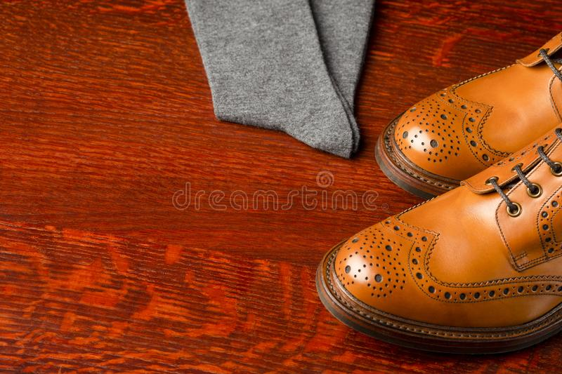 Footwear Compositions Made Up of Mens Fashionable Tanned Brogues. Boots and Pair of Socks Placed Together. Over Wooden Background.Horizontal Image stock photos