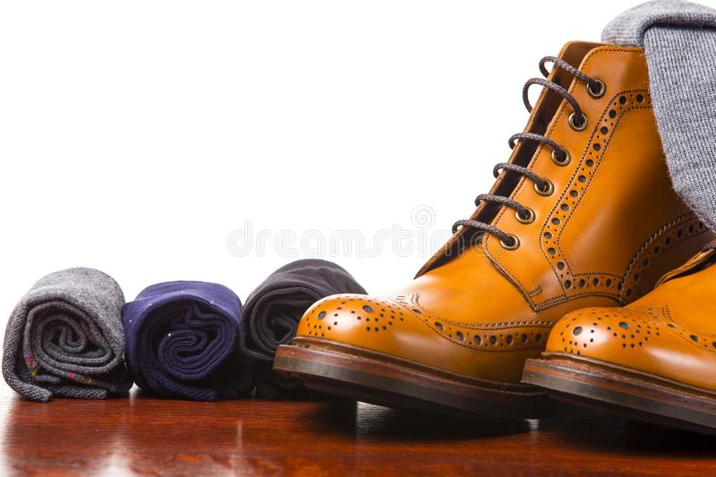 Footwear Compositions Made Up of Mens Fashionable Tanned Brogues. Boots, Warm Hat and Batch of Rolled Colorful Socks Laid Close. Isolated Over White.Horizontal stock photos