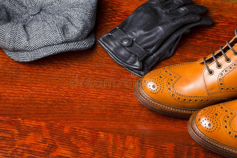 Footwear Compositions Made Up of Mens Fashionable Tanned Brogues. Boots, Warm Hat and Leather gloves Laid Together. Over Wooden Background.Horizontal Image royalty free stock photo