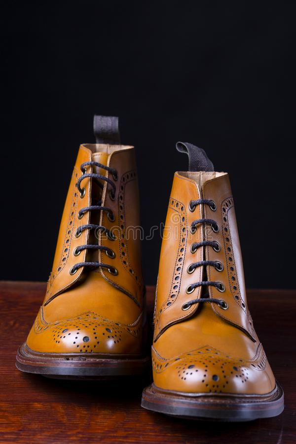 Footwear Compositions Made Up of Mens Fashionable Tanned Brogues. Boots Isolated Over Black.Vertical Image stock photography