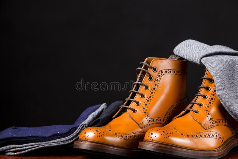 Footwear Compositions Made Up of Mens Fashionable Tanned Brogues. Boots, Warm Hat and Batch of Socks Laid Close. Isolated Over Black.Horizontal Image stock image