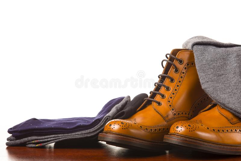 Footwear Compositions Made Up of Mens Fashionable Tanned Brogues. Boots, Warm Hat and Batch of Socks Laid Close. Isolated Over White.Horizontal Shot stock photography