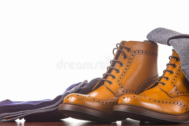 Footwear Compositions Made Up of Mens Fashionable Tanned Brogues. Boots, Warm Hat and Batch of Socks Laid Close. Isolated Over White.Horizontal Image stock photography
