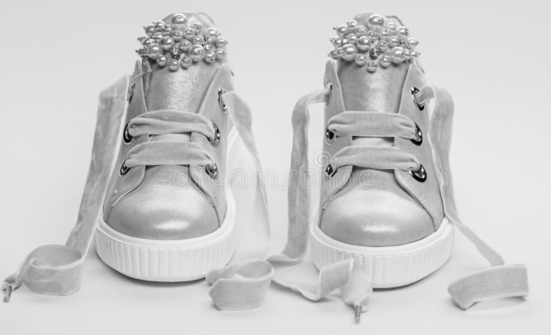 Footwear for girls or women decorated with pearl beads. Pair of pale pink female sneakers with velvet ribbons. Childrens stock images