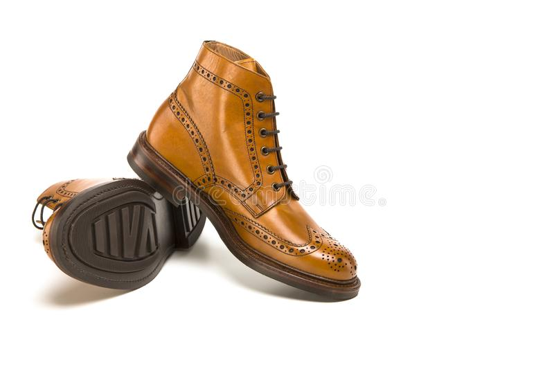 Footwear Ideas. Premium Tanned Brogue Derby Boots. Made of Calf Leather with Rubber Sole. Placed One Over Another. Isolated Over Pure White Background stock photos