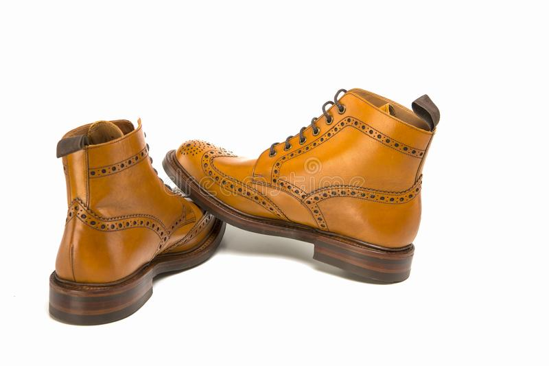 Footwear Ideas. Premium Tanned Brogue Derby Boots Made of Calf L. Eather with Rubber Sole. Placed One Over Another. Isolated Over Pure White Background stock photography