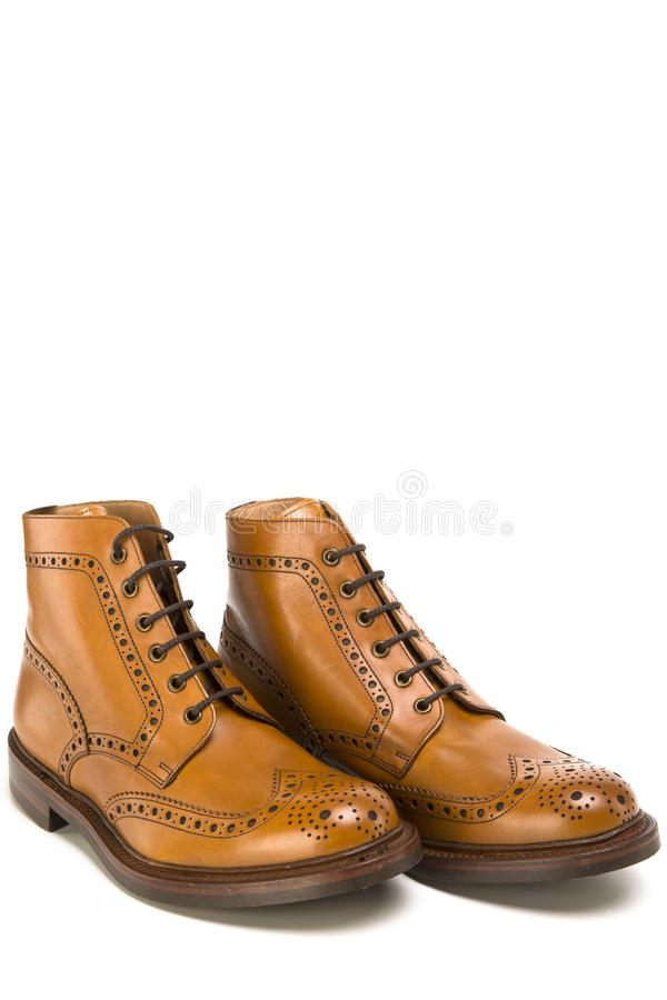 Footwear Ideas. Premium Tanned Brogue Derby Boots Made of Calf Leather. With Rubber Sole. Isolated Over Pure White Background. Vertical Image royalty free stock photography