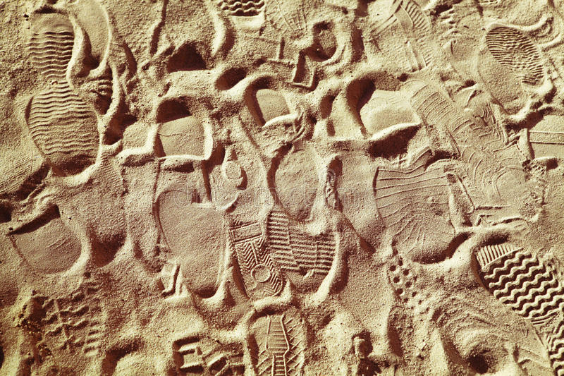 Footwear prints. Prints from various footwear on sand, background royalty free stock photos