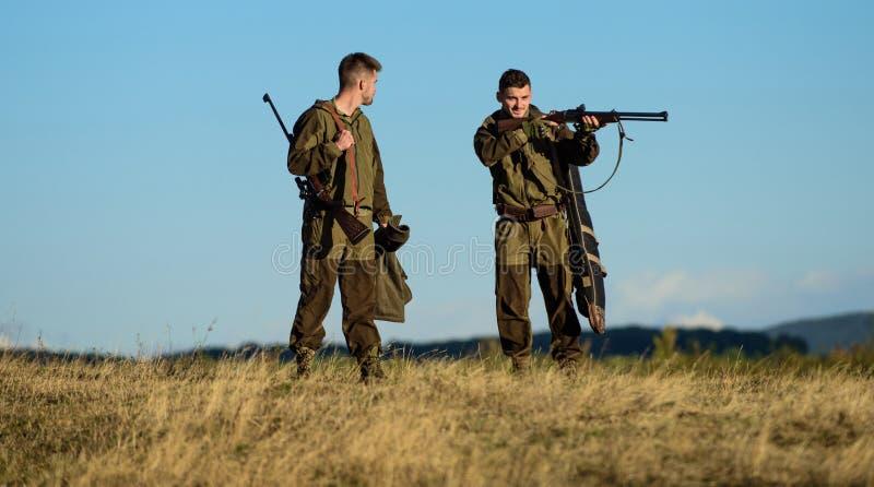 Forças do exército camuflar Amizade de caçadores dos homens Habilidades da caça e equipamento da arma Como caça da volta no passa fotografia de stock