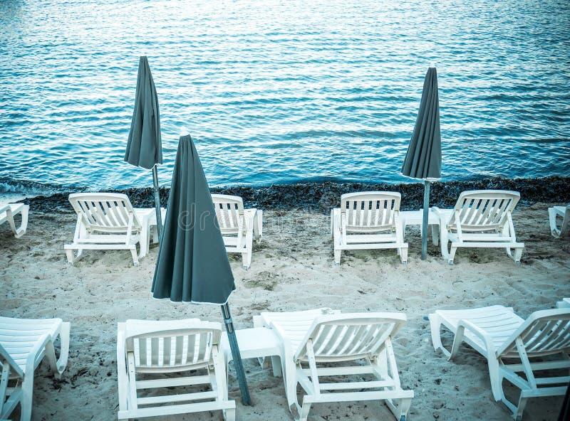 Fora da estação na praia da areia sem povos Guarda-sóis fechados, parasol, cadeiras plásticas brancas, sofás imagem de stock