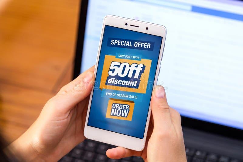 50% fora da venda Menina que guarda um smartphone com uma propaganda do desconto de 50% na tela Mercado, comércio eletrónico, pub imagem de stock