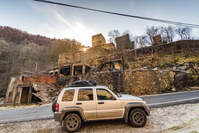 Fora do carro da estrada pela vila queimada abandonada imagens de stock royalty free