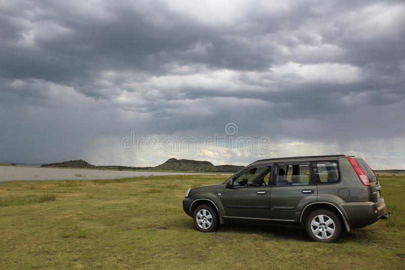 Fora do fim de semana da estrada - um carro de Nissan estacionado na paisagem africana com nuvens de tempestade fotografia de stock