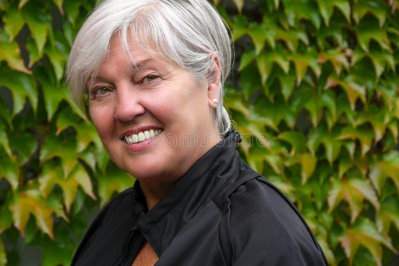Fora do retrato superior idoso de vista agradável de sorriso da mulher com a parede verde das folhas imagem de stock royalty free