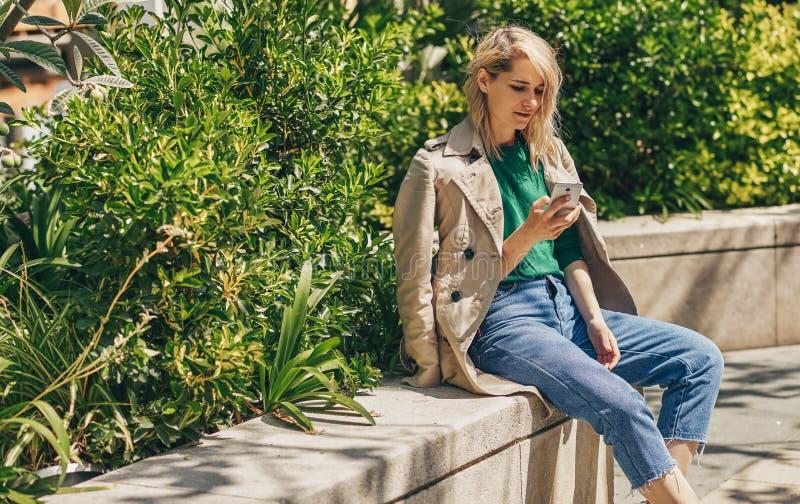 Fora imaget de mensagens no smartphone, assento da escrita da jovem mulher exterior na cidade no dia ensolarado fotografia de stock