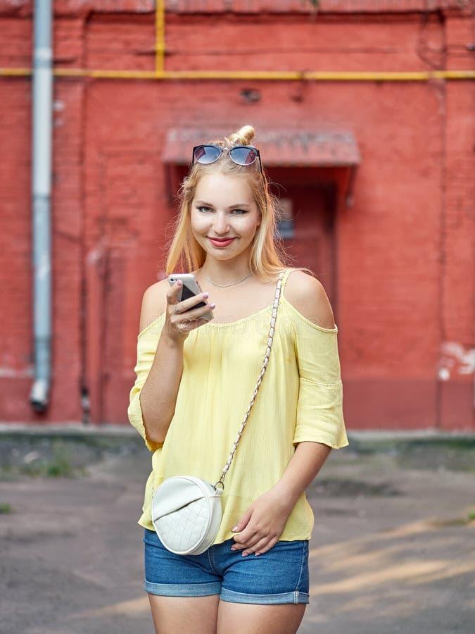 Fora o retrato da mulher loura bonita nova com o short alto das calças de brim do penteado do bolo amarela a blusa que aprecia a  fotos de stock