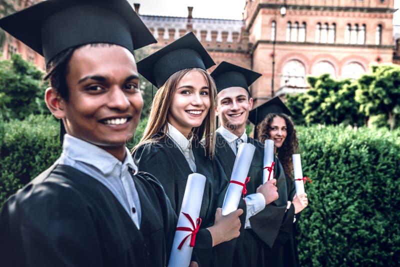 Foram educados e aprontam-se para ir! Os graduados felizes estão estando na universidade exterior nos envoltórios com diplomas à  imagens de stock