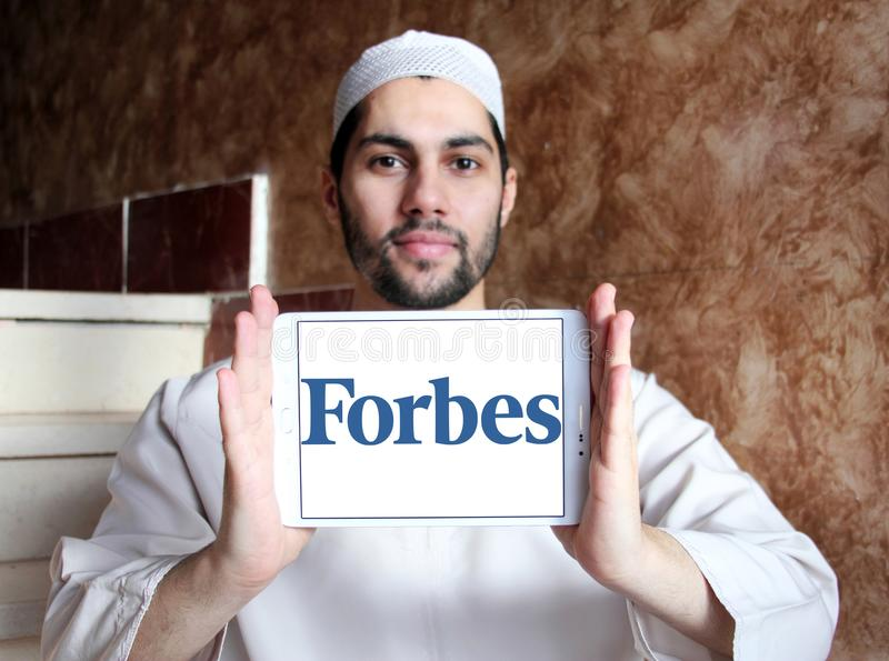 Forbes magazine logo. Logo of Forbes magazine on samsung tablet holded by arab muslim man. Forbes is an American business magazine. it features original articles stock photo