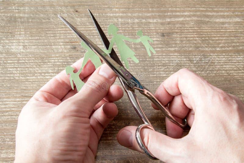 Forbici che tagliano il taglio della carta della famiglia immagini stock