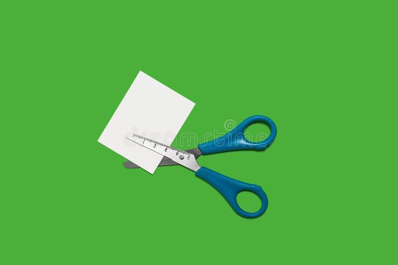 Forbici che tagliano piccola carta fotografia stock libera da diritti