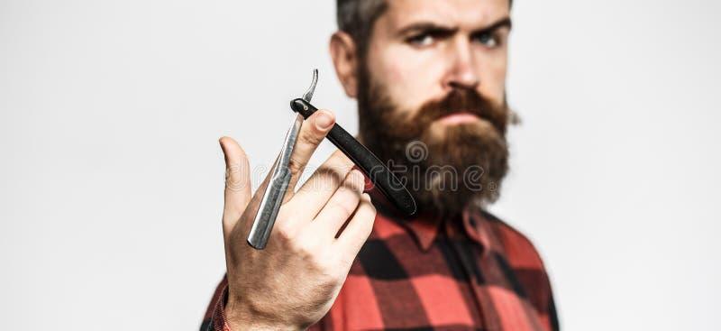 Forbici del barbiere e rasoio diritto, parrucchiere Uomo barbuto, barba lunga, pantaloni a vita bassa brutali e caucasici con i b fotografie stock
