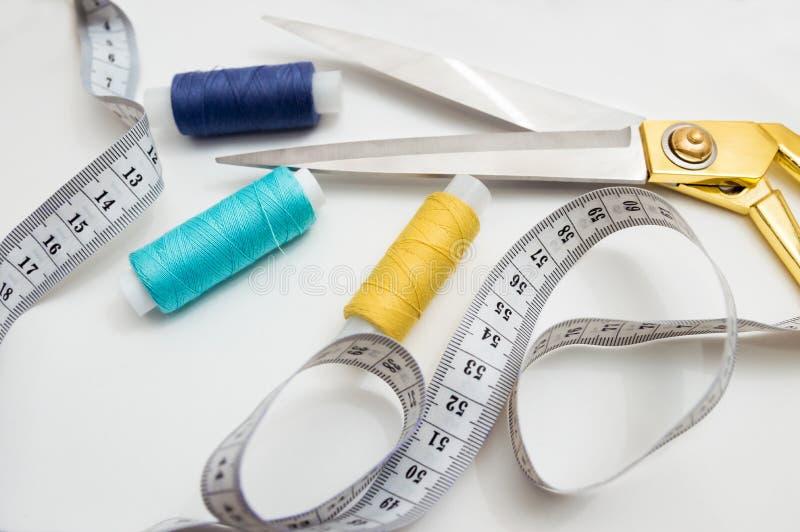 Forbici dorate, fili blu, blu e gialli, nastro di misurazione che si trovano su un fondo bianco, un insieme per il taglio e cucir fotografia stock libera da diritti