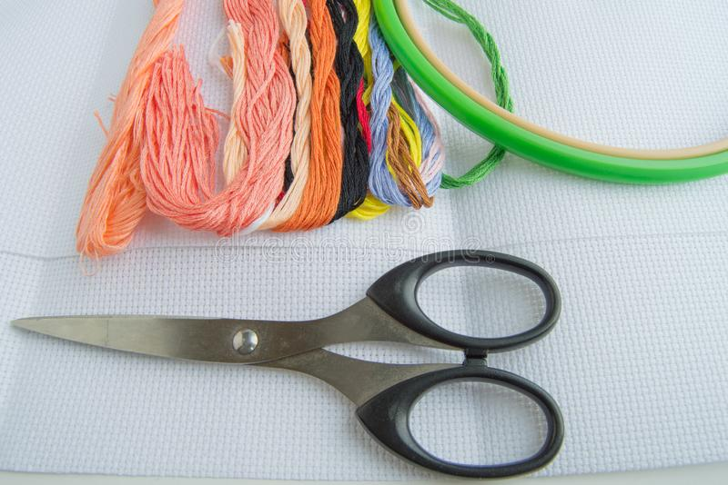 Forbici e filo variopinto luminoso per il filo del ricamo su tela Accessori fatti a mano su fondo bianco Posto per testo, superio fotografie stock