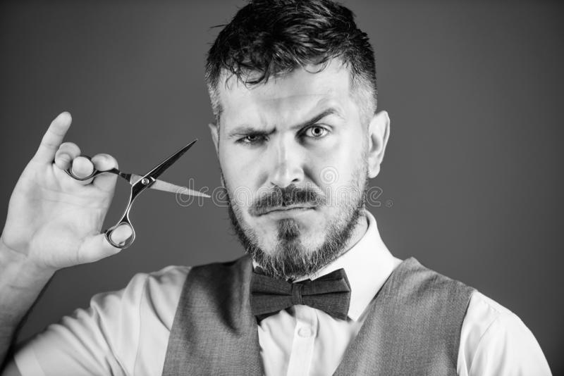 Forbici rigorose della tenuta del fronte dell'uomo d'affari Barbiere con le forbici d'acciaio della tenuta dei baffi e della barb immagine stock