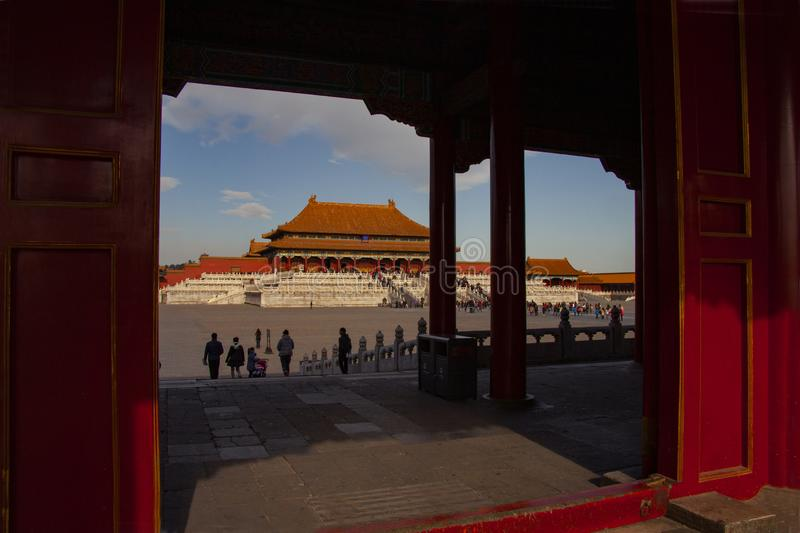 The forbidden city in Beijing. Chinese imperial palace from the Ming Dynasty. View over the Harmony Square through the shadows of. A gate with the Hall of stock image