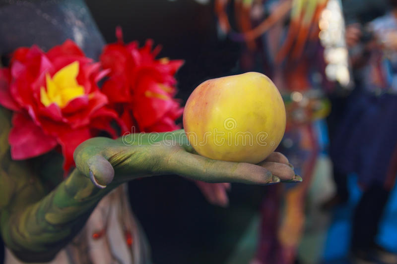 Forbidden fruit in the hand of the devil royalty free stock images