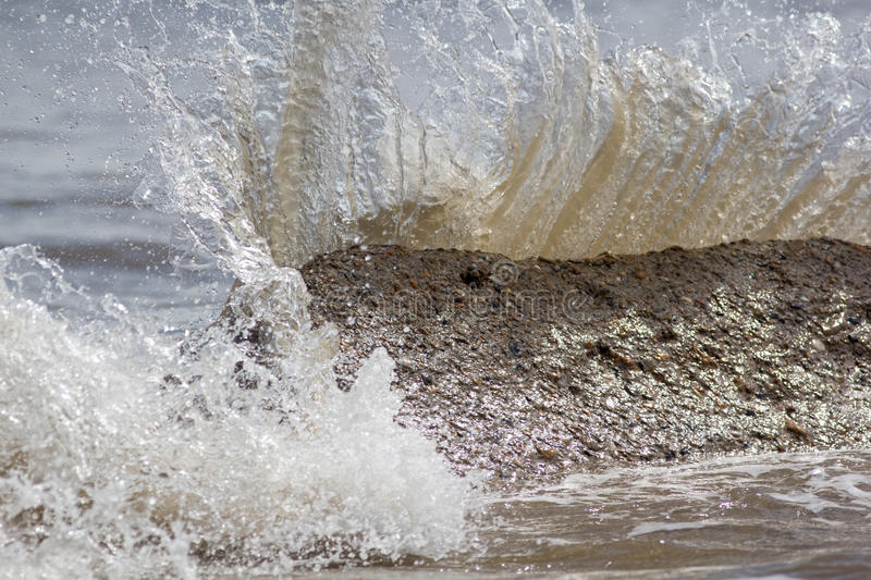 Force of nature. Splashing wave energy. Splash as sea water hits. Concrete rock. Fast shutter speed freezes water splashing. Image connotations of natural stock images