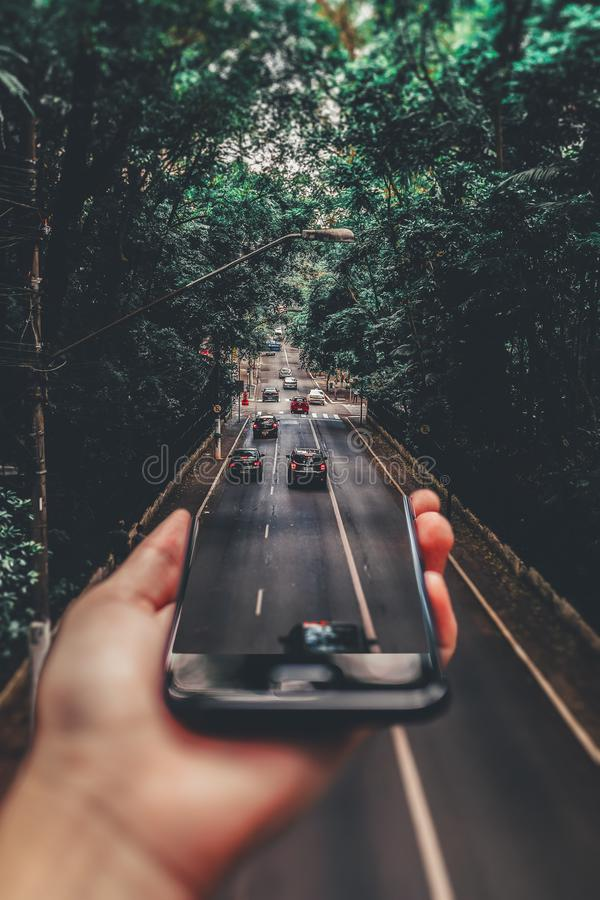 Forced Perspective Photography of Cars Running on Road Below Smartphone royalty free stock images