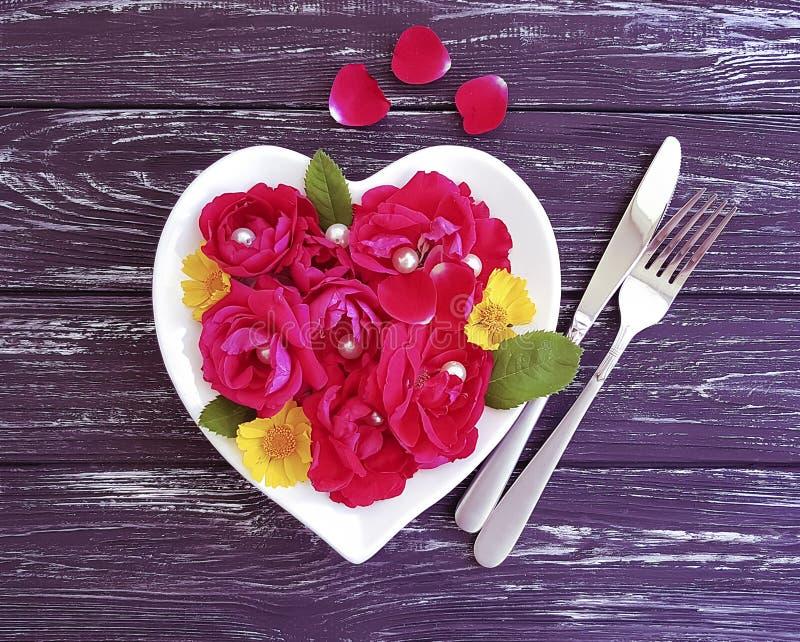 forcella, coltello, cuore del piatto, evento rosa del fiore su fondo di legno immagine stock