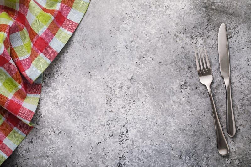 Forcella, coltello e tovaglia a quadretti su una tavola con una struttura concreta Priorità bassa dell'alimento fotografia stock libera da diritti
