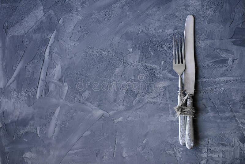 Forcella d'annata e coltello su un backgroun concreto con lo spazio della copia immagini stock libere da diritti