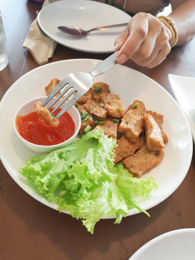 Forcella della tenuta della mano che pugnala braciola di maiale fritta sul piatto bianco con la salsa di peperoncini rossi fotografia stock