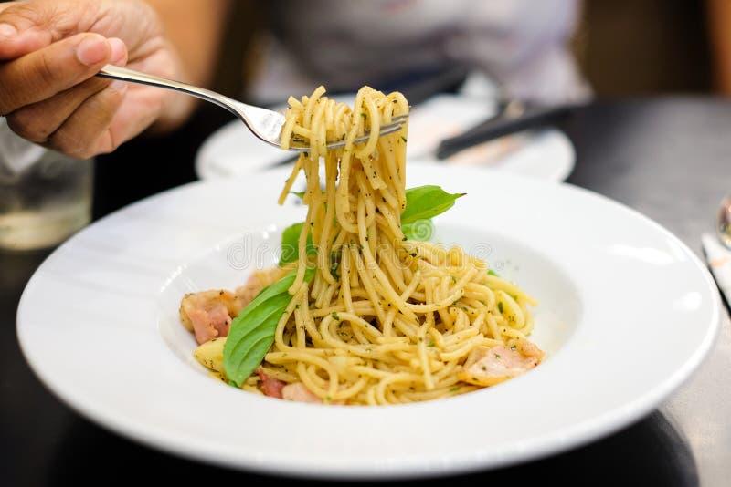 Forcella della tenuta della mano del ` s della donna per il cibo il bacon & del prosciutto piccanti degli spaghetti immagini stock